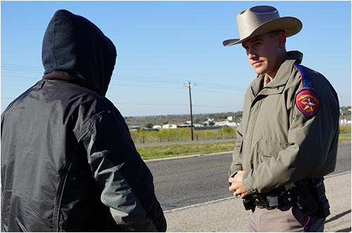 Stock image of an officer of the Texas Department of Public Safety talking to a suspect on the side of a road.