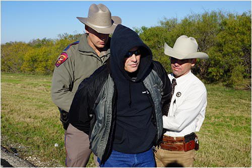 Stock image of a Texas Department of Public Safety officer and another officer arresting a suspect.