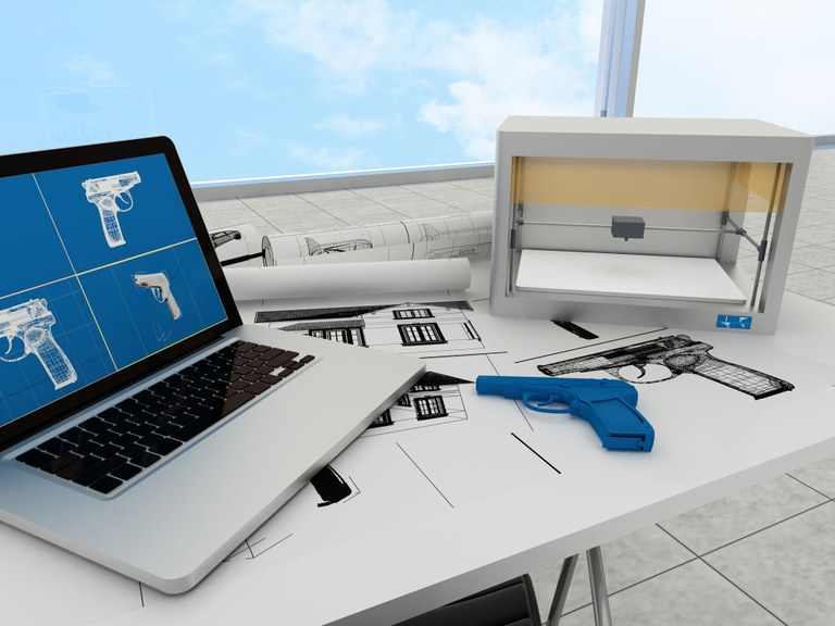 Stock image of a laptop, 3D printer, and plastic handgun.