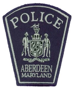 "The Aberdeen, Maryland, Police Department patch focuses on the Maryland state seal as the central image. The graphic displays the farmer and the fisherman, symbols of Maryland's primary industries during colonial times, standing on either side of the coat of arms for Cecilius Calvert, the 2nd Lord of Baltimore. Calvert was an English colonizer and the first proprietor of Maryland. The banner below the seal displays the Latin motto ""Fatti Maschii, Parole Femine,"" which translates to ""Manly Deeds and Womanly Words."""