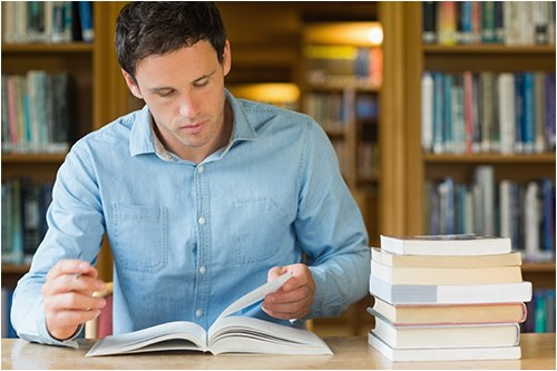 Stock image of a man studying in a library.