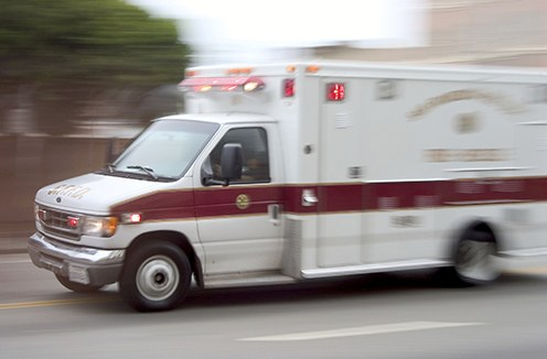 Stock image of an ambulance driving fast on a road.