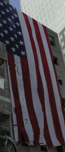 A tattered American flag hangs from a building damaged by the 9/11 attack in New York City.
