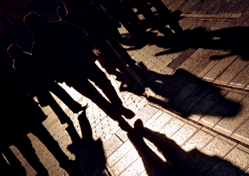 Angled Silhouettes and Shadows of People Walking (Stock Image)