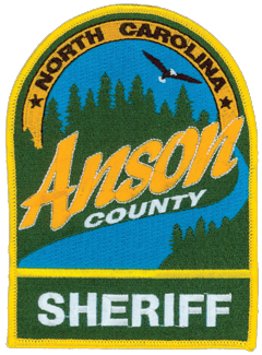 Anson County, North Carolina is located on the southern border of the state and makes up 553 square miles of rural countryside. Established in 1750, the county initially stretched from the Atlantic Ocean to the Mississippi River. The patch of the Anson County Sheriff's Office depicts a vast pine forest amidst a wide open, blue sky and one of the rivers that border the county. Also featured is a soaring bald eagle, often found along the area's rivers.