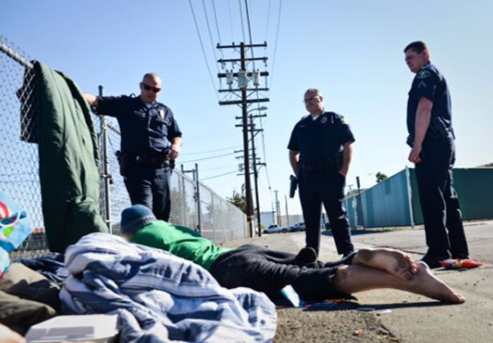 Law enforcement officers are depicted assisting a homeless man on the side of a road.