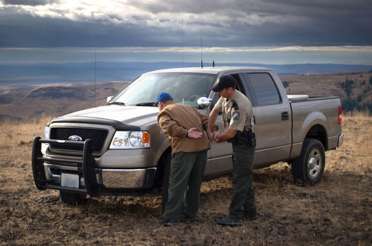 Wildlife officer arresting suspect in front of truck. Photo from Washington Department of Fish and Wildlife.