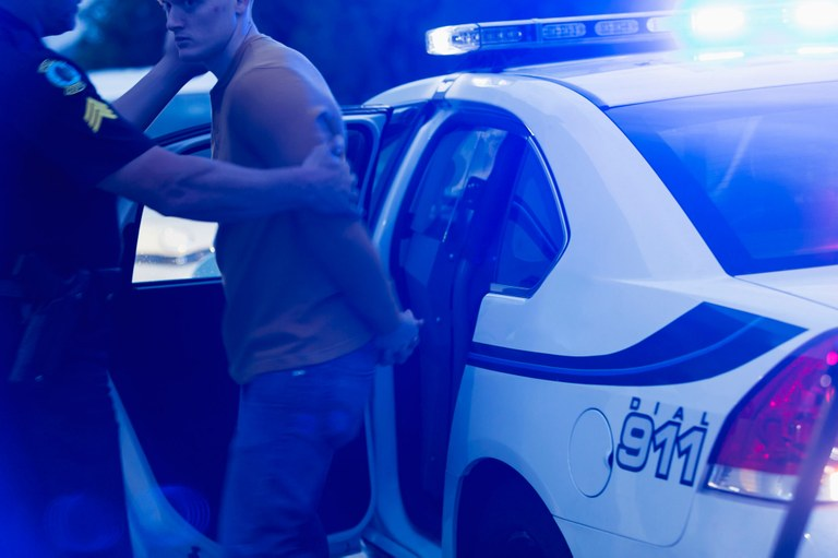Stock image of a male in handcuffs being placed in police car.