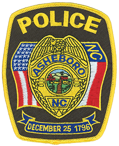 The badge of the Asheboro, North Carolina, Police Department is prominently depicted on the agency's service patch. The Asheboro city seal is featured in the center. Within the seal is a depiction of a plank road that ran through the city in the 1700s, a prominent church from Asheboro's early days, and a textile factory. The flags of the United States and North Carolina are shown to the left and right of the badge, respectively. The banner at the bottom displays the date on which Asheboro was chartered—Christmas Day, 1796.