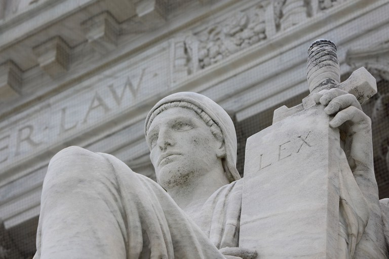 Stock image of the Authority of Law Statue in front of the U.S. Supreme Court Building.