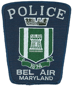 The patch of the Bel Air, Maryland, Police Department prominently features the coat of arms of the town it serves. The crenellated mural crown at the top represents Bel Air's sovereignty as the county seat of Harford County, while the five merlons symbolize the town's five-commissioner form of government. The green shield in the center denotes the fertile fields of the county, with the tower in the middle symbolizing the town. The two silver pales on either side of the tower represent Bel Air's location between the silvery waters of Winters Run to the west and Bynum Run to the east. The banner at the bottom marks the year the town was incorporated and the Bel Air Police Department was founded.