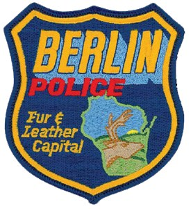 "The Berlin, Wisconsin, Police Department patch features the outline of the state with its beautiful hills and sunsets. The city calls itself the ""Fur and Leather Capital"" because it serves as the home to many such stores, as represented by the large buck."