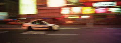 A blurred police car driving down a city street.