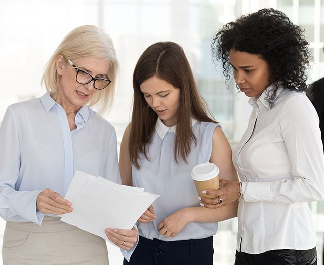 Stock image of a business manager looking at paperwork with two younger employees.