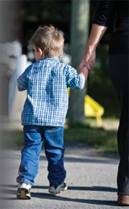 A child is pictured walking through a playground, guided by a parent, guardian, or perhaps stranger.