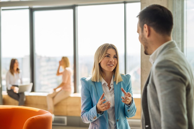 Stock image of a male and female talking in a business setting.