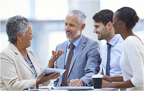 Stock image of four people standing and talking.