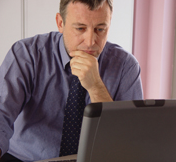 Stock image of a businessman working on a laptop computer. © Thinkstock.com