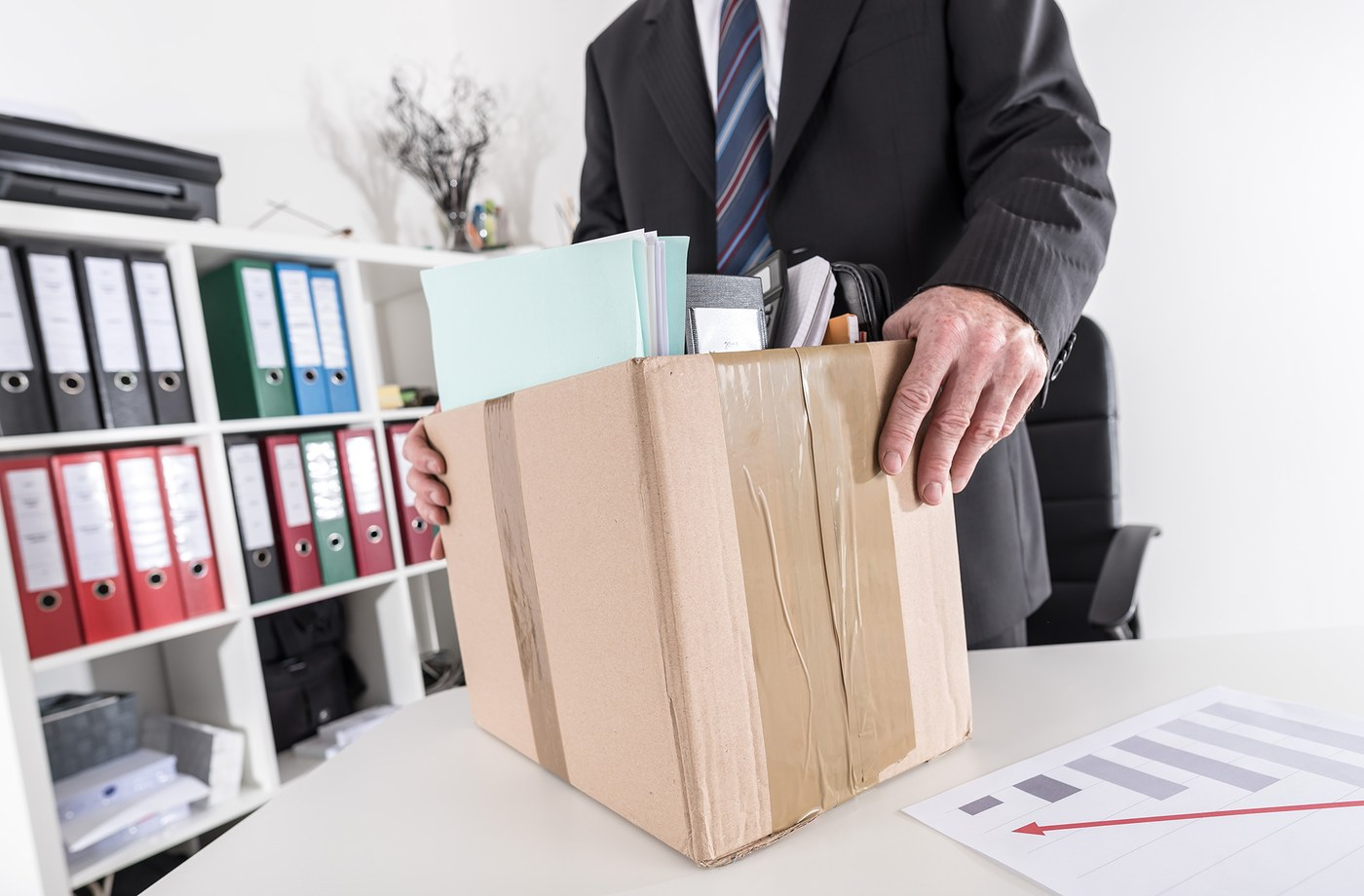 Businessman holding box with office items.