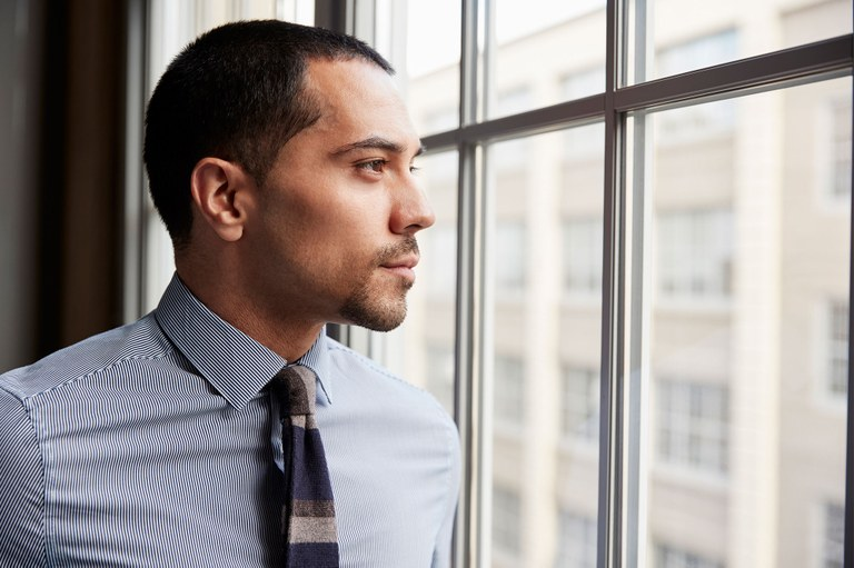 A stock photo of a business professional looking out of a window.