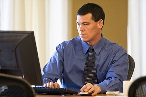 Stock image of a man wearing a tie working on a computer in an office.