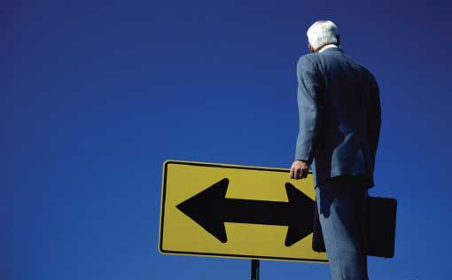 Businessman Standing in Front of Road Sign with Two-Directional Arrow (Stock Image)