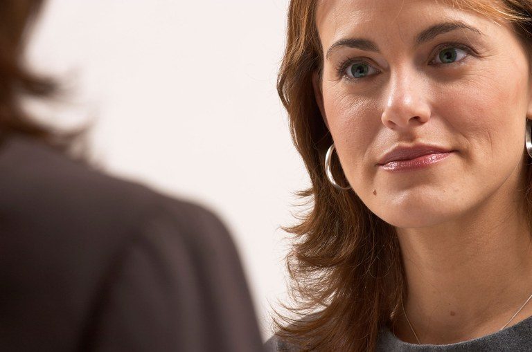 Stock image of a business woman listening to another female.