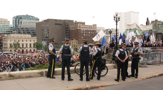 A group of Canadian police officers with crowds of people nearby.