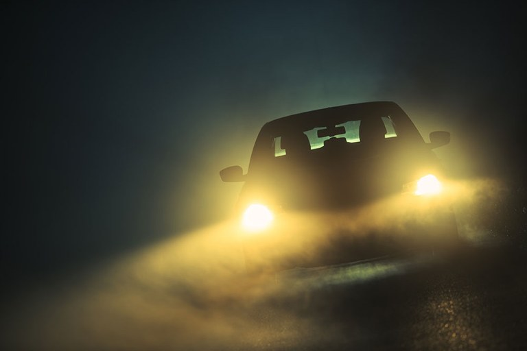 A stock image of a car with headlights on at night.