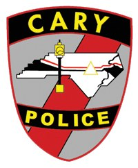 The patch of the Cary, North Carolina, Police Department was developed in 1996 by a local artist. The state is depicted in the center of the patch, superimposed by a clock that stands in the city's historic downtown. The triangle represents the area of the state where Cary is located—between Raleigh, Durham, and Chapel Hill, known as the Research Triangle Park.