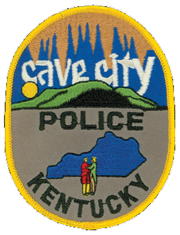 True to its name, Cave City, Kentucky, is in close proximity to the world's longest known system of caves, the over-390-mile Mammoth Cave National Park. Visitors to the park fuel the tourism industry on which the city thrives. As such, the patch of the Cave City Police Department pays homage to the caves with the stalactites hanging from above. Also depicted on the patch are the rolling hills of Kentucky and a layout of the commonwealth superimposed by the two men portrayed on the Seal of Kentucky.