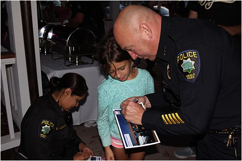 Menlo Park (California) Police Chief Robert Jonsen and Officer Alcaraz sign autographs at a Friday Night Lights community outreach event.