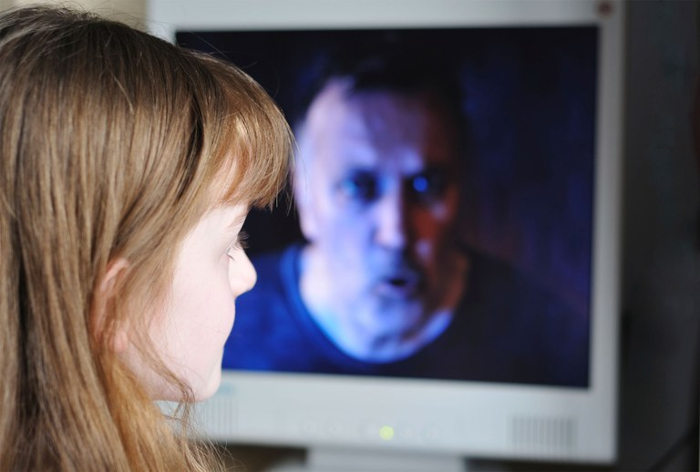 A photo of a young girl in front of a computer screen containing an image of a man.