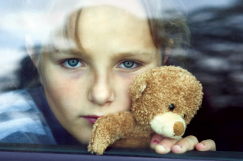 Stock image of a child holding a teddy bear and staring out of a car window.