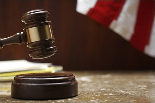 Stock image of a gavel about to hit a sound block with a flag in the background.