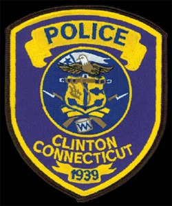 The Clinton, Connecticut, Police Department patch prominently displays the town's official seal, which includes an eagle, an anchor, two flintlock rifles, and a military drum. In the center of the seal, two small images highlight the industries that first supported the town's early population: a plow, symbolizing agriculture, and a fish, illustrating the fishing community. The year 1939 indicates the date when the Connecticut General Assembly passed legislation to establish the town's police department.