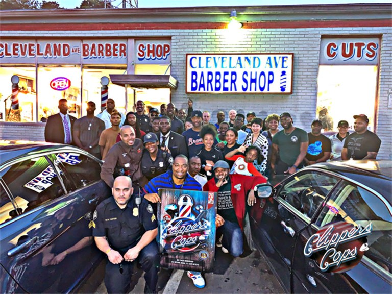 A photo of a group of citizens and officers posing outside of a barbershop with a Clippers and Cops sign.
