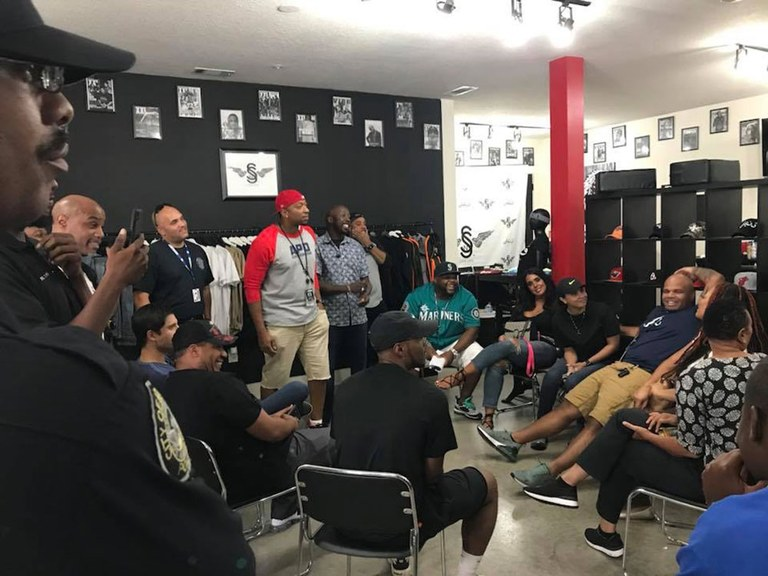 A photo of a Clippers and Cops meeting taking place in a barbershop.