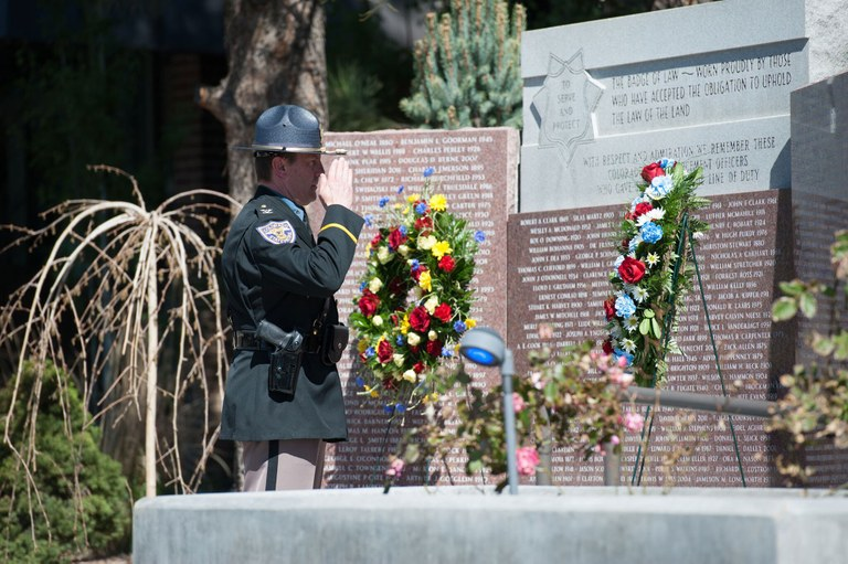 An officer saluting an engraved wall at the Colorado Law Enforcement Memorial at Camp George West, in Golden, Colorado.