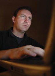 Stock image of a man looking intensely at a computer.