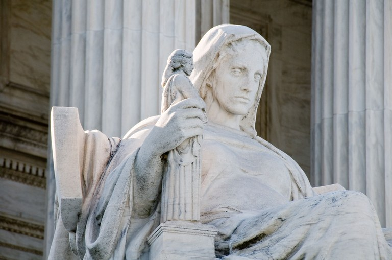 A stock image of the Contemplation of Justice statue located in front of the U.S. Supreme Court Building.