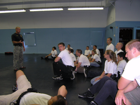 Students crouch on ground during control and arrest tactics training.