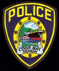 Coos Bay, Oregon, is the largest deep-water shipping port between San Francisco, California, and Portland, Oregon. As such, the city's police department patch illustrates the town's importance to the West Coast shipping industry. Log ships and tug boats, like those featured in the center of the patch, routinely maneuver through the city's historical industrial bay.