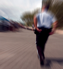 Stock image of a police officer running toward the scene of an incident.
