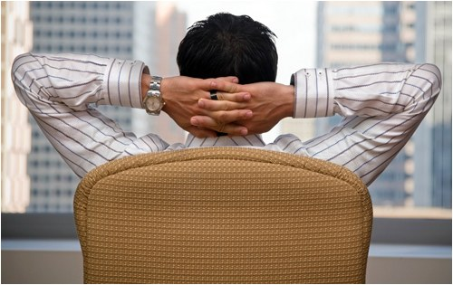 Stock image of a man sitting in a chair with his hands behind his head looking out at a city skyline.