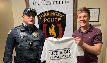 An image of a Torrington officer with a teenager holding a t-shirt from the Caught Doing Something Right youth program.