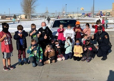 An image of two Torrington officers with a group of young children.