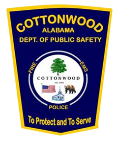 On the patch of the Cottonwood, Alabama, Department of Public Safety is a circle acknowledging police, fire, and EMS services that protect the town, established in 1903. The town's namesake, the cottonwood tree, is featured. Also shown are the American flag, recognizing the patriotism of the community; a church, indicating the importance of religion among citizens; and a bear, representing the sports mascot of the local high school and signifying times past when bears roamed the area.