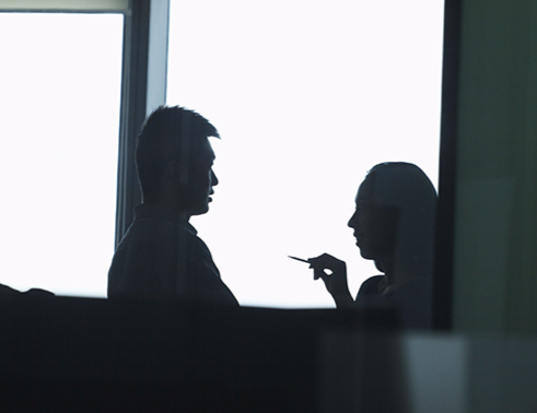 Stock image of a man and woman talking near a window.