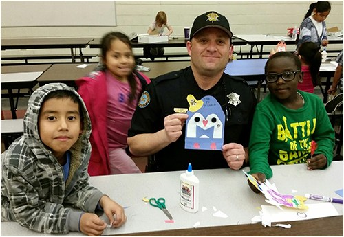 Community Police Officer Kerby Tonalea working on a penguin art craft project with kids as part of the Scottsdale, ArizonamPolice Department's Partnering Law Enforcement and Youth (P.L.A.Y.) program.